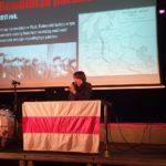 Anton Zhivanow siedzący za stołem przystrojonym we flagę białoruską, biało-czerwono-białą. Trzyma w dłoni mikrofon. W tle ekran z wyświetloną prezentacją historyczną.