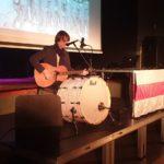 Anton Zhivanow siedzi na scenie z gitarą akustyczną przed mikrofonem. Śpiewa i gra na gitarze i bębnie. W tle ekran z prezentacją.