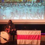 Anton Zhivanow siedzi na scenie z gitarą akustyczną przed mikrofonem. Śpiewa i gra na gitarze i bębnie. W tle ekran z prezentacją. Po prawej stół z biało-czerwono-białą flagą.