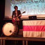 Anton Zhivanow stoi na scenie z gitarą elektryczną. Śpiewa, gra na gitarze i bębnie.