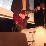 Anton Zhivanow stoi na scenie z gitarą elektryczną. Śpiewa, gra na gitarze i bębnie. Zbliżenie.
