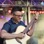 Gitarzysta grający na gitarze akustycznej. W tle oświetlenie sceniczne.