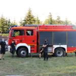 Wóz straży pożarnej. Przed pojazdem trzech strażaków.