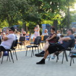 Widzowie siedzący na krzesełkach przed sceną. Widok z boku.