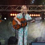Dziewczyna stojąca na scenie przed mikrofonem z gitarą. W tle światła i dym.