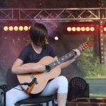 Dziewczyna siedząca na scenie z gitarą.