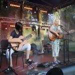 Dwie dziewczyny na scenie z gitarami. Jedna siedzi, druga stoi przed mikrofonem.