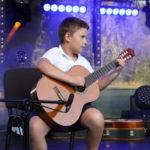 Chłopiec na scenie gra na gitarze siedząc.