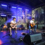 Dwóch chłopców na scenie. Grają na gitarach siedząc. W tle oświetlenie sceny.