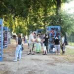 Wystawa zdjęć z okazji 50-cio lecia działalności MOK. Kilkanaście osób, konstrukcje ze zdjęciami, drzewa.