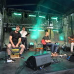 Na scenie od prawej: Tomasz Budzyński z gitarą, gitarzysta elektryczny, perkusista z kajonem. W tle konferansjer.