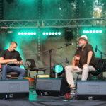 Na scenie od prawej: Tomasz Budzyński siedzący z gitarą przed mikrofonem, siedzący gitarzysta elektryczny.