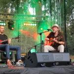 Na scenie od prawej: Tomasz Budzyński z gitarą, gitarzysta elektryczny.