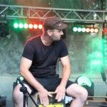 Na scenie, perkusista siedzący na kajonie.