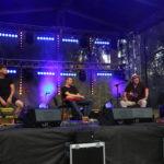 Na scenie od prawej: Tomasz Budzyński z gitarą, gitarzysta elektryczny, perkusista z kajonem.