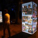 Wystawa zdjęć z okazji 50-cio lecia działalności MOK. Wieczór, ciemno, podświetlone konstrukcje ze zdjęciami, drzewa, widzowie.