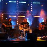 Na scenie siedzący Grzegorz Kupczyk z gitarą przed mikrofonem. Po lewej i po prawej dwóch siedzących gitarzystów z gitarami akustycznymi.