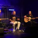 Na scenie siedzący Grzegorz Kupczyk przed mikrofonem. Po lewej i po prawej dwóch siedzących gitarzystów z gitarami akustycznymi. Niebieskie światło sceniczne.