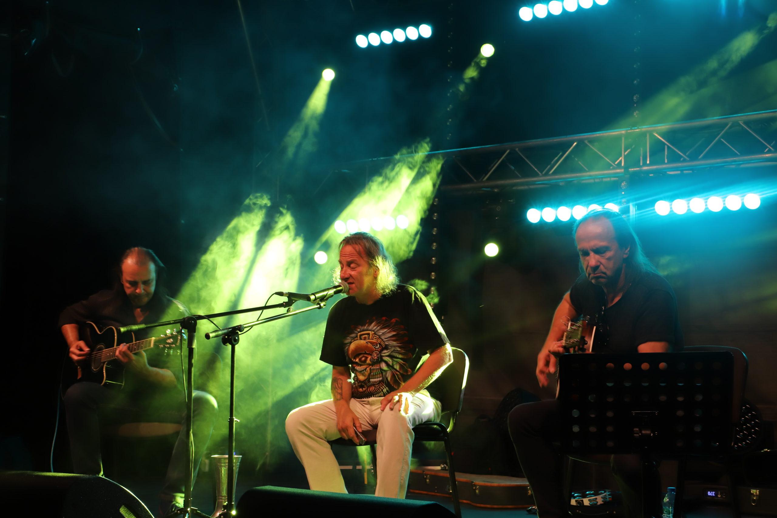 Na scenie siedzący Grzegorz Kupczyk przed mikrofonem. Po lewej i po prawej dwóch siedzących gitarzystów z gitarami akustycznymi. Zielone światło sceniczne.