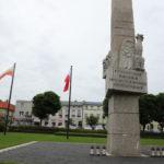 """Po prawej """"Pomnik pamięci"""" na Placu 20 Października w Mosinie. Po lewej widoczna kamienica i dwie flagi w barwach RP i Mosiny."""