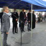 Po lewej przemawiający dyrektor Mosińskiego Ośrodka Kultury, po prawej przedstawiciele władz Gminy Mosina i proboszcz mosińskiej parafii i przybyli mieszkańcy.