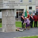 """Starsza kobieta odkładająca znicz pod """"Pomnik pamięci""""."""