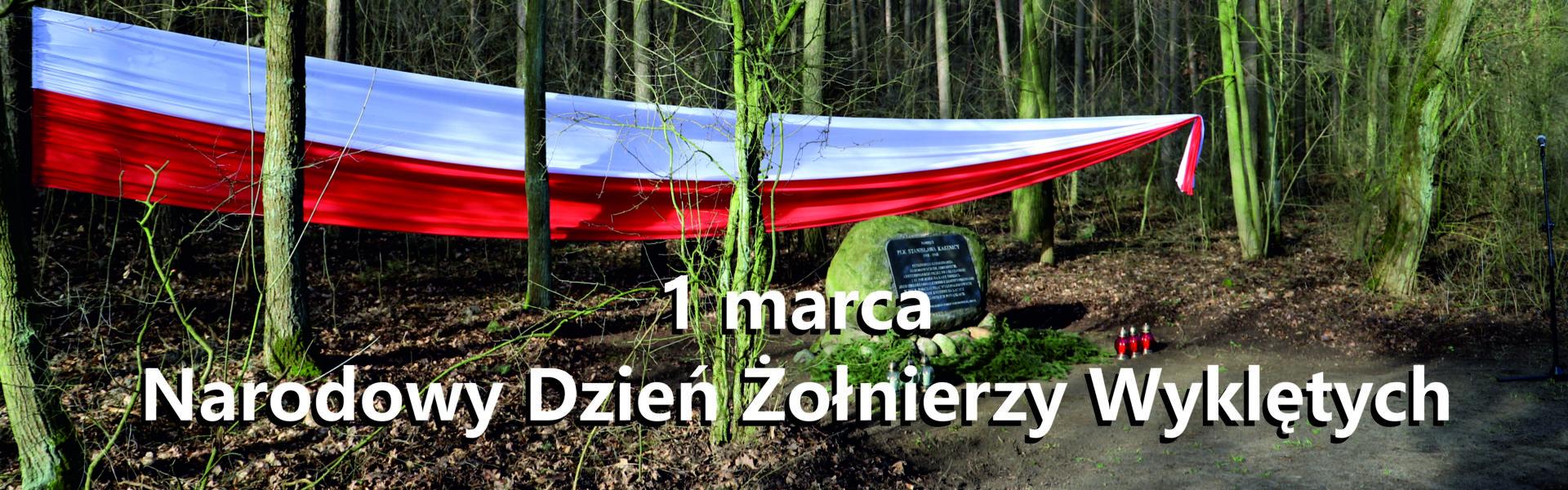 Baner informujący o Narodowym Dniu Żołnierzy Wyklętych pierwszego marca. Flaga Polski rozwieszona między drzewami. Fragment lasu i kilka drzew przed flagą. W centrum kamień pamiątkowy i znicze.