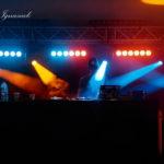 DJ na scenie oświetlony strumieniami światła pomarańczowego i niebieskiego.