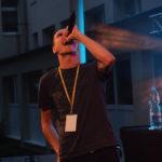 Śpiewający wokalista na pierwszym planie, w tle budynek szkoły.