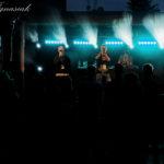 Oświetlona scena z oddali. Na scenie trzech wykonawców. Na pierwszym planie sylwetki widzów.