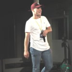 Stojący artysta na scenie. Nie śpiewa, trzyma mikrofon na wysokości klatki piersiowej.
