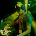DJ na scenie przed konsolą w zielonym świetle.