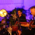 Na scenie, siedzący gitarzysta z gitarą akustyczną i perkusista z djembe.