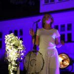 Na scenie, stojąca wokalistka przed mikrofonem, w tle podświetlony na granatowo budynek szkoły.