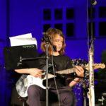 Na scenie, gitarzystka grająca na gitarze elektrycznej siedząc. W tle podświetlony na granatowo budynek szkoły.