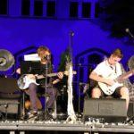 Na scenie, gitarzysta i gitarzystka grający na gitarach elektrycznych siedząc. W tle podświetlony na granatowo budynek szkoły.