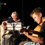 Na scenie, gitarzysta i gitarzystka grający na gitarach akustycznych siedząc.