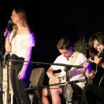 Na scenie, po lewej stojąca wokalistka przed mikrofonem, po lewej dwóch siedzących gitarzystów.