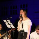 Na scenie, na pierwszym planie stojąca wokalistka przed mikrofonem, w tle dwóch siedzących gitarzystów.