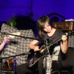 Na scenie, siedząca gitarzystka.