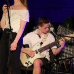 Na scenie, siedzący gitarzysta z gitarą elektryczną, przed nim niepełna postać wokalistki.