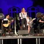 Na scenie, stojąca wokalistka, za nią troje siedzących gitarzystów.