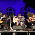 Na scenie, troje siedzących gitarzystów z gitarami akustycznymi.