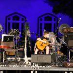 Na scenie, gitarzysta siedzący z gitarą klasyczną.