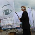 Anna Krenz trzymająca transparent z firanki z namalowanym okiem. Na oczach ma opaskę z firanki.