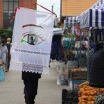 Anna Krenz idzie przez targowisko miejskie z transparentem z firanki. Na transparencie namalowane oko.