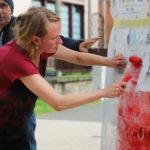 Anna Krenz maluje wałkiem na czerwono firankę umieszczoną na słupie ogłoszeniowym.
