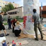 Trzy osoby malują czerwoną farbą białą firankę okrywającą słup ogłoszeniowy. Po lewej chłopiec przy drabinie i mężczyzna z wałkiem malarskim.