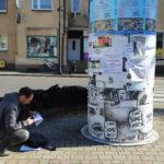 Roman Bromboszcz okleja słup ogłoszeniowy na Placu 20 Października w Mosinie
