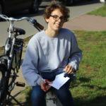Osoba z rowerem przygotowuje napis do naklejena na słupie
